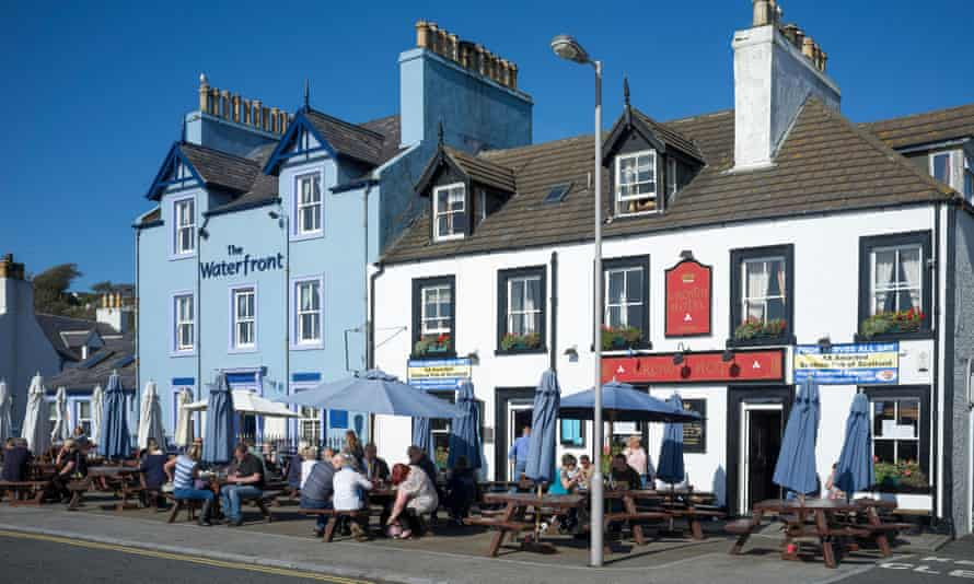 People enjoying drinks in the sunshine outside The Waterfront Hotel and The Crown Hotel in Portpatrick, Dumfries & Galloway, UK.