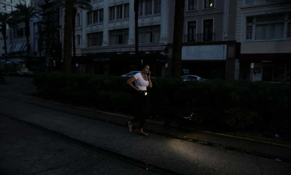 A woman walks her dog in downtown New Orleans at dawn during a blackout in the city after Hurricane Ida.