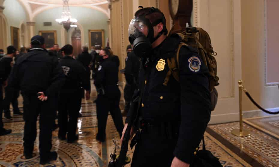 A US Capitol police officer wears a gas mask.