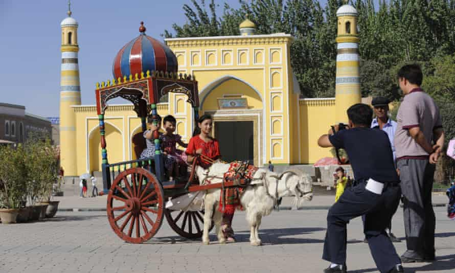 Children ride in a goat-drawn carriage in Kashgar, Xinjiang. Poets and researchers have warned that Uighur poetry is on the verge of extinction as Beijing detains and silences poets.