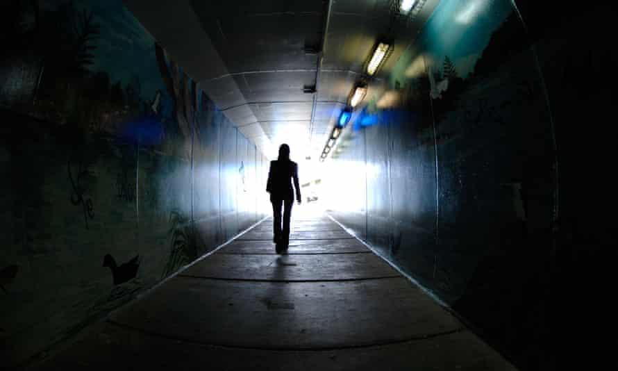 A woman walking through a dark tunnel alone