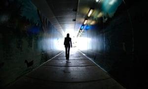 Woman walking through a dark tunnel