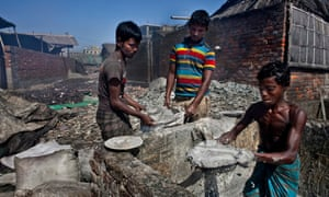 Mohammad Alamgir, 24, Mohammad Hasan, 16, and Biplop Mohammad, 13, bag animal fat that will be turned into soap.