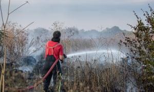 A firefighter controls a large grass fire near Heathrow