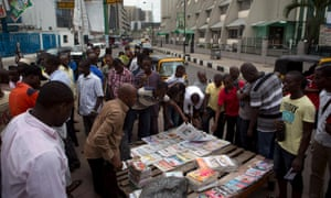 Men read newspaper headlines on a street in Lagos as they await election results.