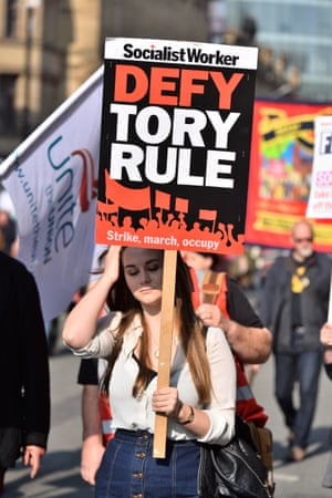 Protester holding a 'defy Tory rule' Socialist worker banner at anti-austerity march in Manchester