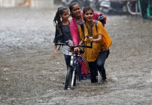 Ahmedabad, IndiaGirls battle through a waterlogged road during the monsoon