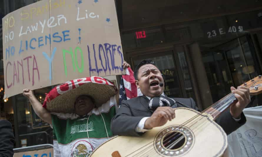 A demonstrator dances and sings along the Mariachi Tapatio de Alvaro Paulino band as they perform during a demonstration across the street from the building that once housed the office space of Aaron Schlossberg Friday in New York.