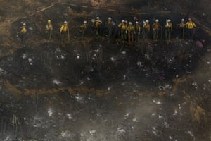 Hand crews line up to work on the remaining hot spots from a brush fire