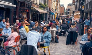 People dine at outdoor tables in London