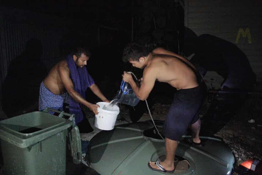 Refugees pull water from a makeshift well