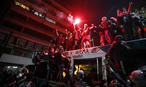 A group of protesters destroys a bus during an anti-government protest, in Santiago, Chile, on Friday.