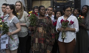 People hold flowers as they attend a vigil outside Finsbury Park mosque. 'For too long, Muslims have been cast as a risk to public safety and security'.