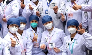 Medical workers pose for photos after a Fangcang makeshift hospital was officially closed at Wuhan International Convention & Exhibition Center on March 9, 2020 in Wuhan, Hubei Province of China.
