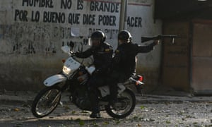 A riot policeman on a motorcycle points his gun during clashes with anti-government demonstrators in the neighborhood of Los Mecedores, in Caracas, on Wednesday.