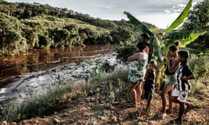 Aline Tiberio, Claudio de Almeida, and their children Kaio, Isabelly and Kaua, look at the mining waste covering some of Parque de Cachoeira.