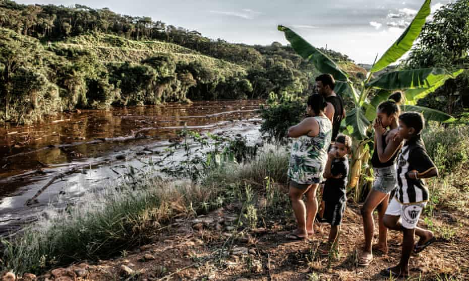 Aline Tiberio, 36, Claudio de Almeida, 39, and their children Kaio, 5, Isabelly, 10 and Kaua, 8, look at the waste from the mine leak.