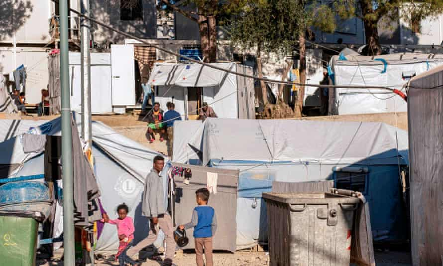 Adults and children walk inside the Moria refugee camp on Lesbos Island in November 2018.