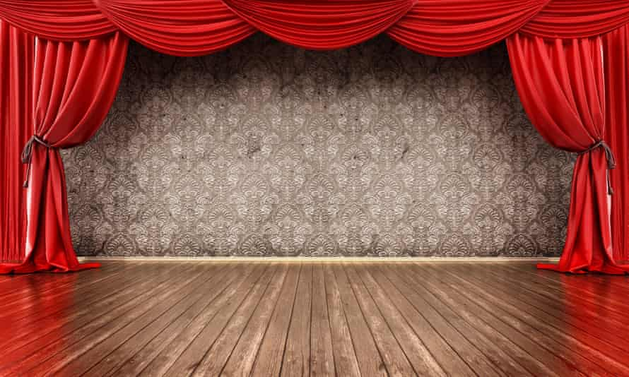 An empty stage framed by a red curtain