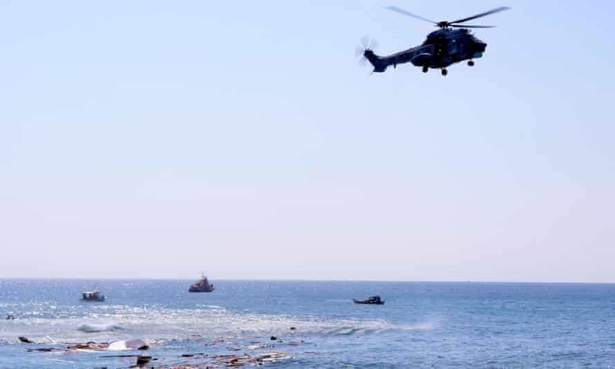 A helicopter flies over the wreckage of a migrant boat, near Greece.