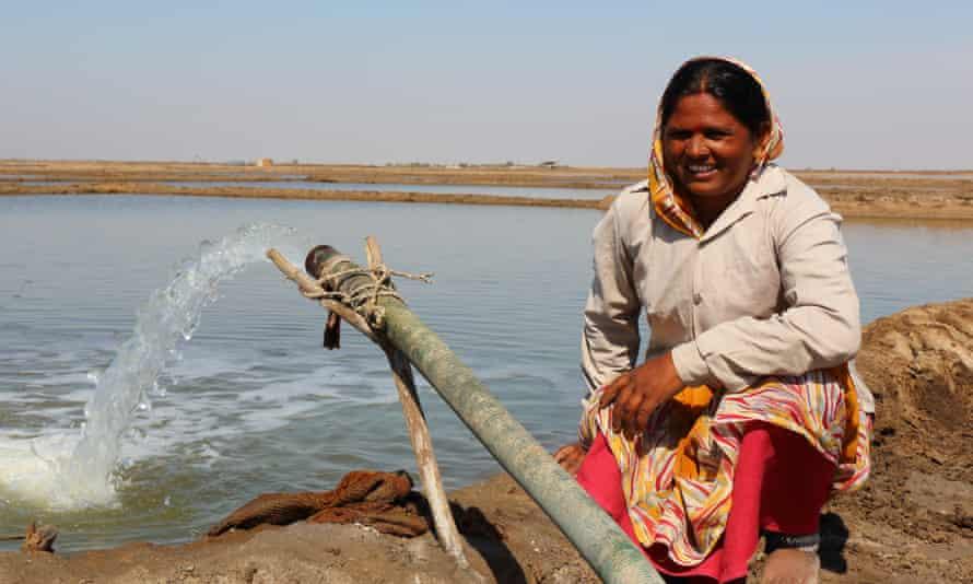 Salt farmer Kirti Ben beside her pumped brine pipe