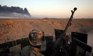 Smoke billows in the background as Iraqi pro-government forces advance towards the city of Fallujah.