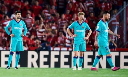 Lionel Messi walks off as Gerard Piqué (left) and Frenkie de Jong try to process Barcelona's defeat at Granada.