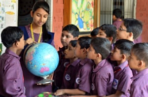Assam, India - A girl uses a globe to teach younger pupils during a discussion on Earth Day at a school in Nagaon