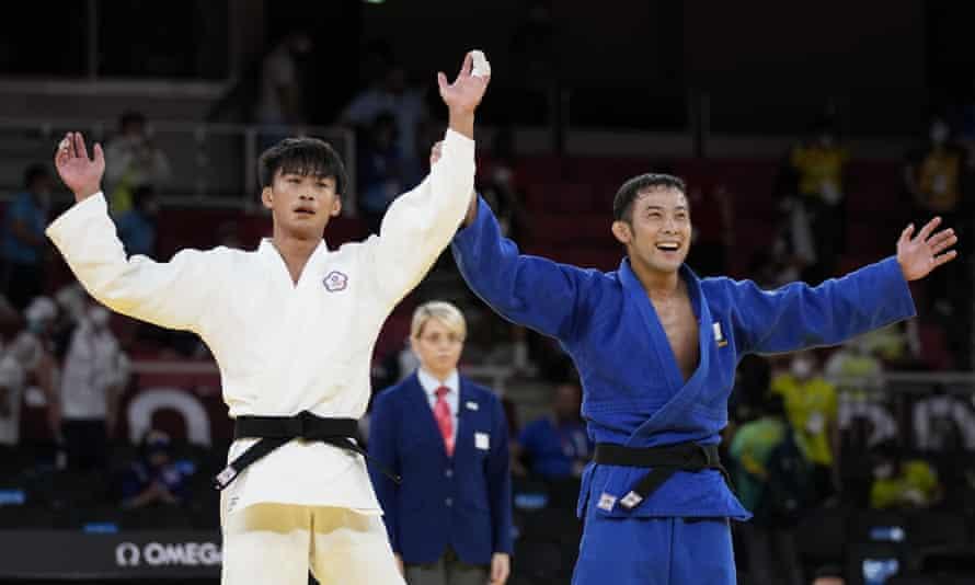 Japan's Naohisa Takato, in blue, celebrates gold in the men's under 60kg judo.