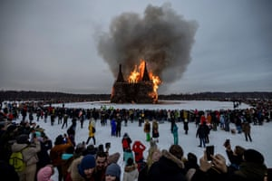 People watching the burning wooden structure