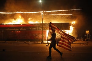 A protester carries the carries a U.S. flag upside, a sign of distress, next to a burning building