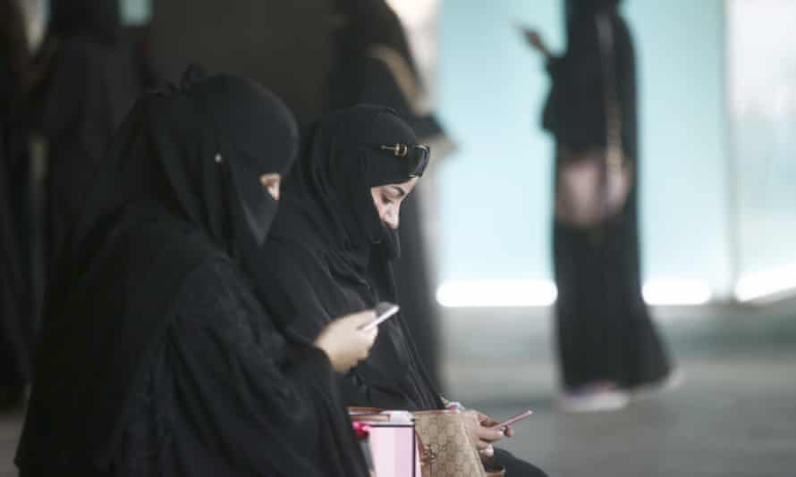 Female shoppers wearing traditional Saudi Arabian dress check their smartphones whilst waiting for transport outside the mall.