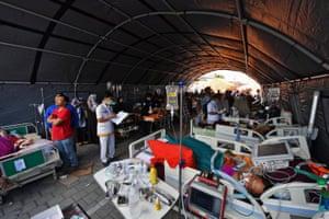Injured quake victim receive medical help at a makeshift ward set up outside a hospital in Mataram.