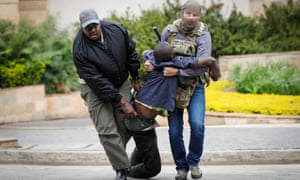 An SAS member helps escort an injured man from the scene of the attack on a hotel complex in Nairobi