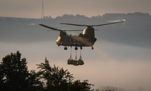 A Chinook helicopter prepares to drop sandbags onto the dam wall at Toddbrook reservoir.