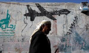 A Yemeni man walks past graffiti depicting a US drone.