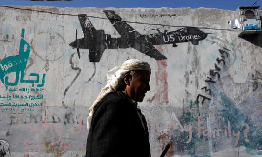 A Yemeni man walks past graffiti depicting a US drone.