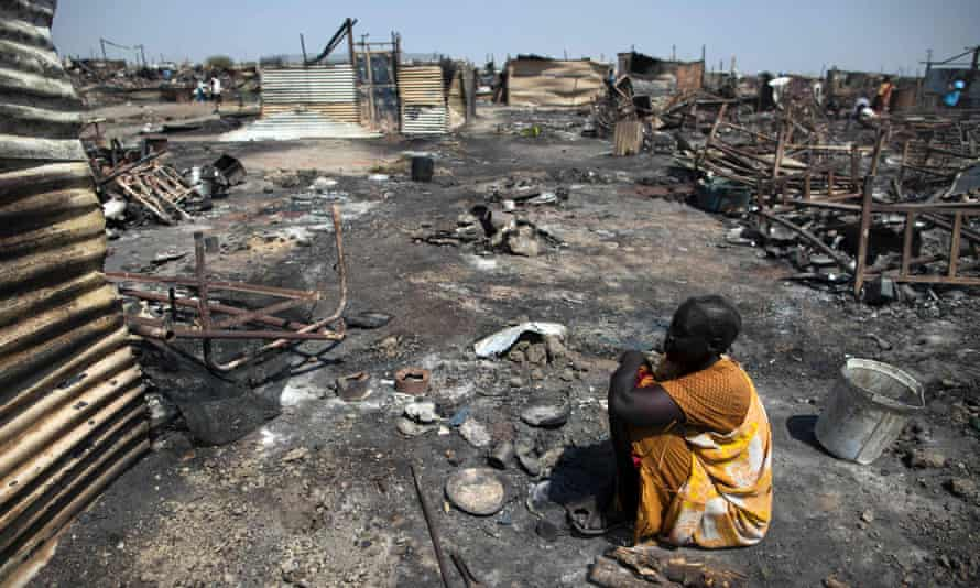 A displaced woman, Akki Adduok, sits in the spot where her shelter used to be in the Protection of Civilians site in Malakal, South Sudan