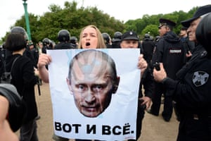 A demonstrator in St Petersburg holds a poster featuring the face of the Russian president, Vladimir Putin, above the words 'That is all'
