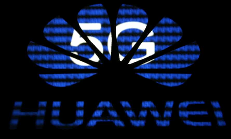 A 3D printed Huawei logo is seen in front of displayed 5G words