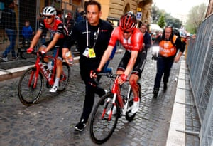 Tom Dumoulin is escorted by a staff member after coming down in the crash on stage four.