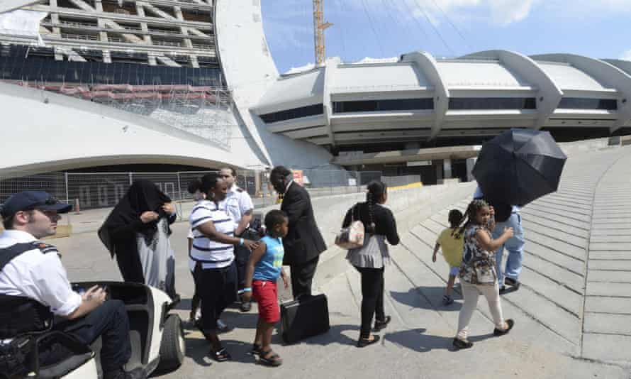 Asylum seekers walk outside Olympic Stadium as security guards look on in Montreal.