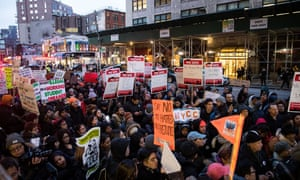 Immigrants and their supporters rally outside a court during a protest against recent immigration raids in New York