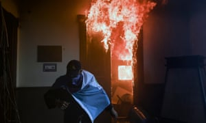 A demonstrator runs after setting an office on fire in the Congress building.
