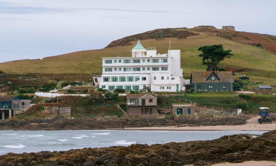 Burgh Island Hotel at the foot of a hill and the with sea in the foreground