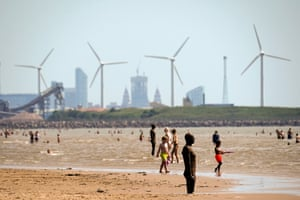 People enjoy the warm weather on Crosby Beach in Liverpool