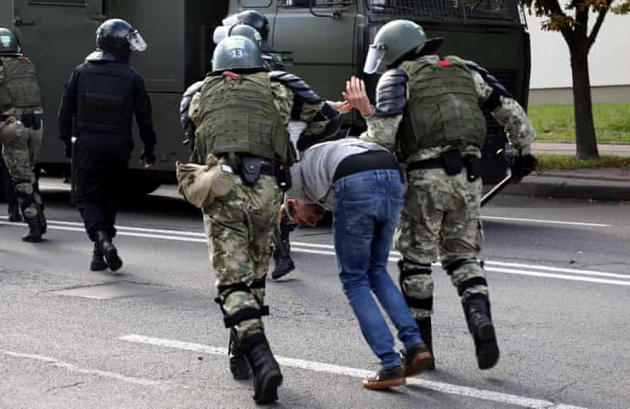 Law enforcement officers detain a man by force on a street in Minsk.
