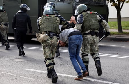 Law enforcement officers forcibly detain a man on a street in Minsk.