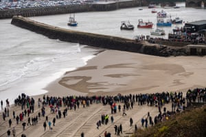 Members of the public gather on Sunny Sands beach, Folkstone, for filmmaker Danny Boyle's Pages of the Sea remembrance project. Portrait of first world war lieutenant and poet Wilfred Edward Salter Owen