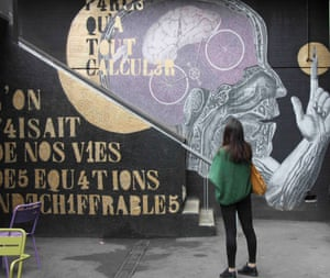 A woman stands in front of street art at Art 42, Batignolles, Paris.